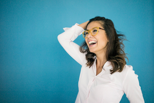 Portrait of laughing woman wearing glasses in front of blue background - gettyimageskorea