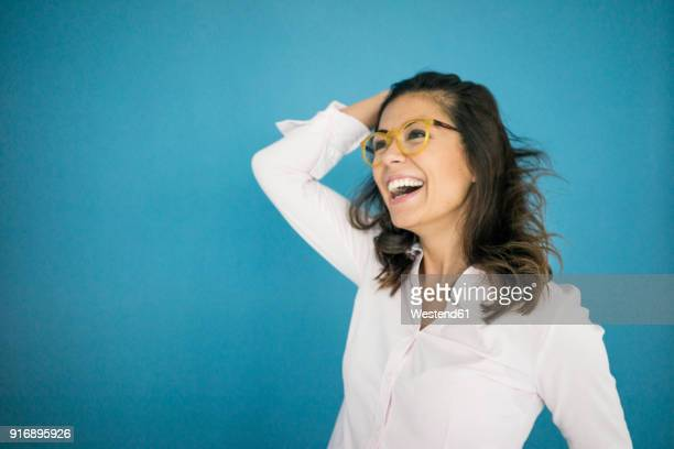 portrait of laughing woman wearing glasses in front of blue background - eccitazione foto e immagini stock