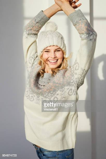 portrait of laughing woman wearing knit pullover and bobble hat - jersey de cuello alto fotografías e imágenes de stock
