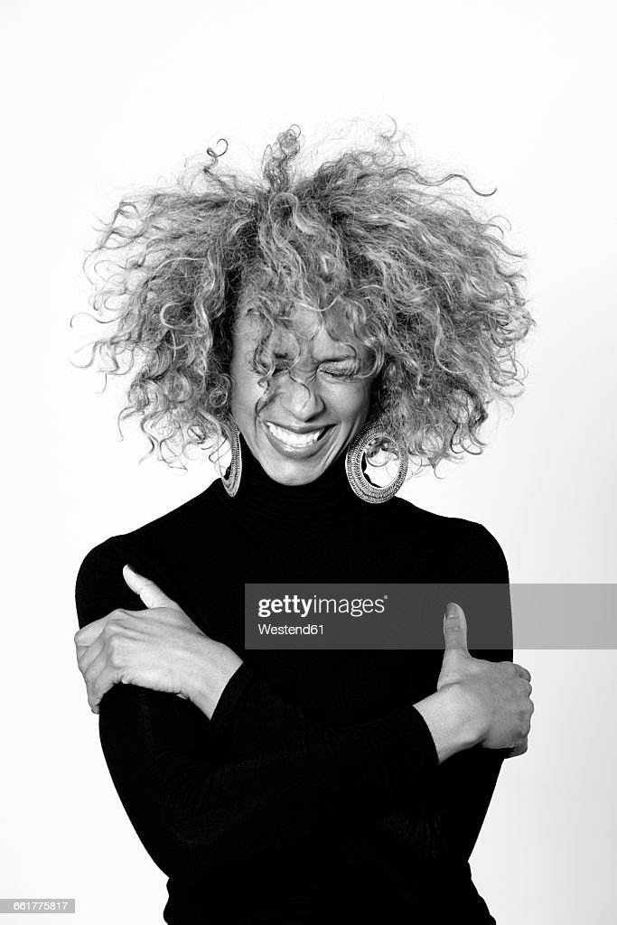 Portrait of laughing woman with afro wearing black turtleneck pullover : Stock Photo