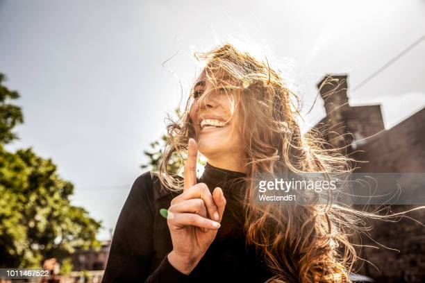 portrait of laughing woman with blowing hair - gegenlicht stock-fotos und bilder
