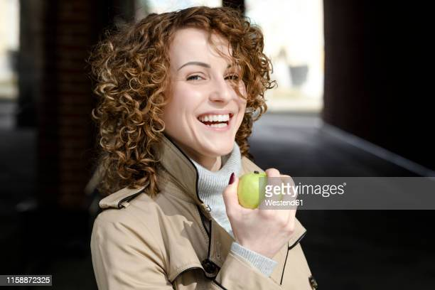 portrait of laughing woman with curly hair with green apple - green coat stock pictures, royalty-free photos & images