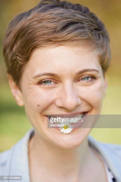 portrait of laughing woman with daisy in mouth - offenes lächeln stock-fotos und bilder