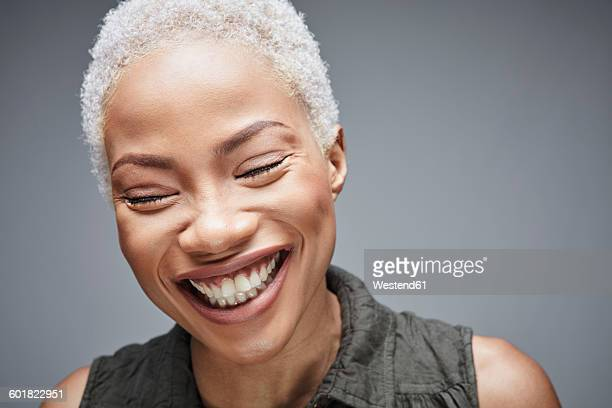 Portrait of laughing woman with eyes closed in front of grey background