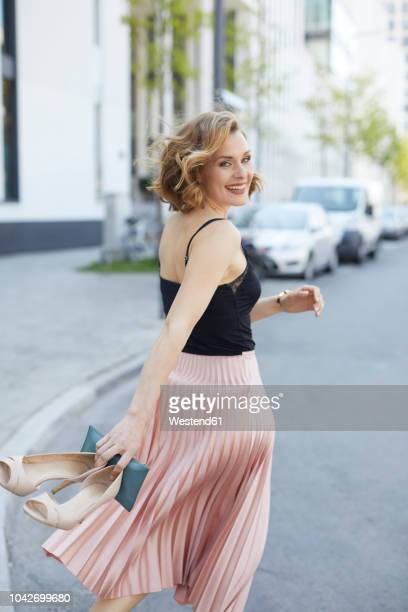 portrait of laughing woman with high heels and clutch bag in her hand walking on the street - vestido largo fotografías e imágenes de stock