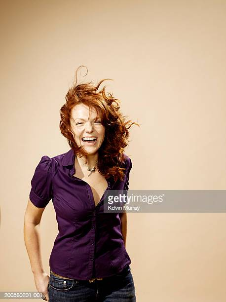 portrait of laughing woman with windswept hair - tousled hair stock pictures, royalty-free photos & images