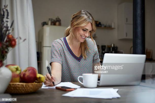 Portrait of laughing woman working on laptop at home