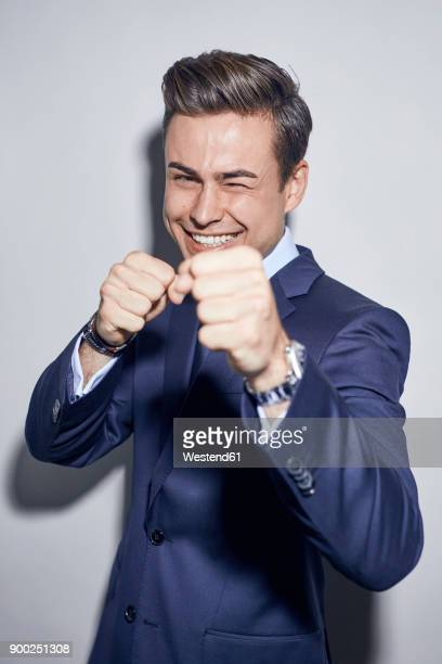 portrait of laughing young businessman boxing - blue jacket stock pictures, royalty-free photos & images