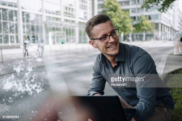 Portrait of laughing young businessman with laptop outdoors