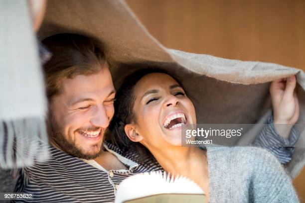 portrait of laughing young couple at home - bettwäsche stock-fotos und bilder