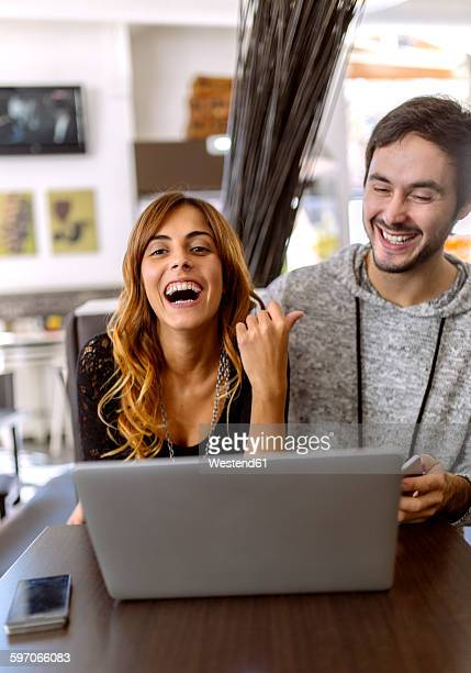 Portrait of laughing young couple with laptop in a pub