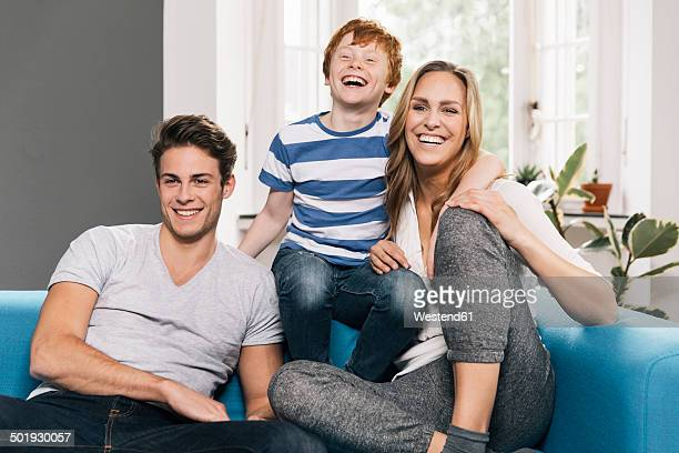 Portrait of laughing young family sitting on their couch at living room