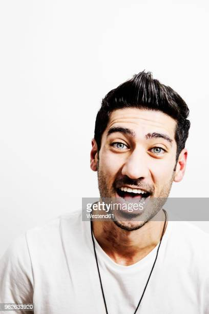 portrait of laughing young man against white background - ポンパドール ストックフォトと画像