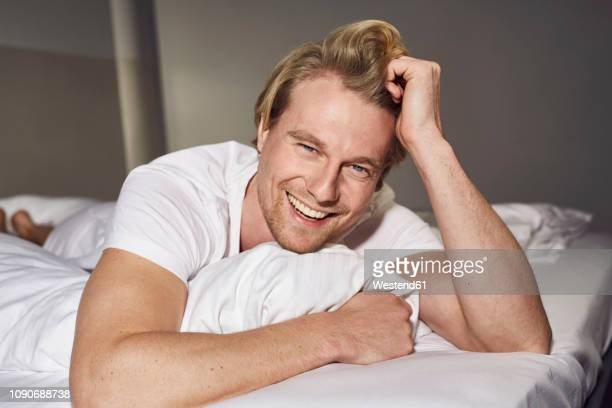 portrait of laughing young man lying on bed - lying on front stock pictures, royalty-free photos & images