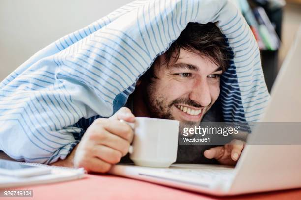 portrait of laughing young man lying on bed with cup of coffee using laptop - mann kaffee stock-fotos und bilder