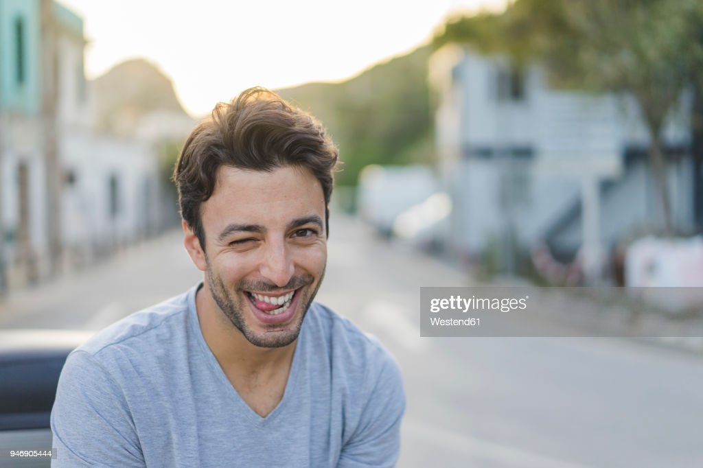 Portrait of laughing young man pulling funny faces : Stock-Foto
