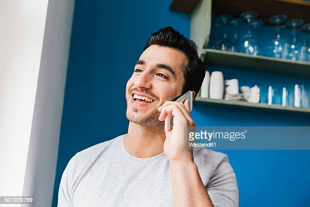 Portrait of laughing young man telephoning with smartphone in his kitchen