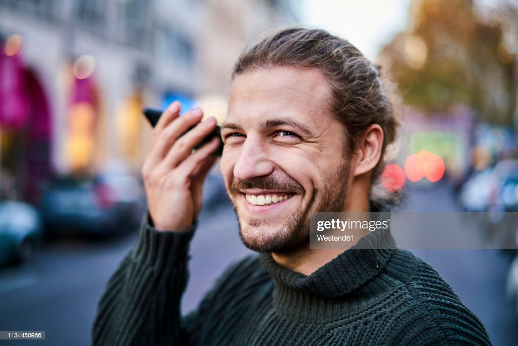 Portrait of laughing young man using smartphone on the street in the evening : Stock Photo