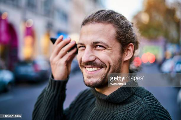 portrait of laughing young man using smartphone on the street in the evening - facial hair stock pictures, royalty-free photos & images