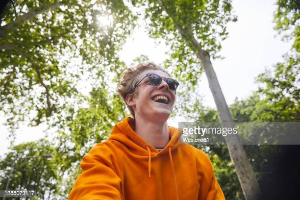 portrait of laughing young man  wearing sunglasses and orange hoodie shirt in nature - オレンジ色のシャツ ストックフォトと画像