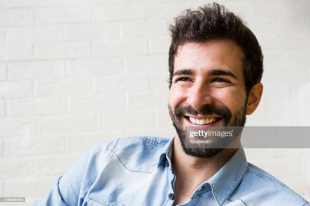 Portrait of laughing young man with beard : Stock Photo
