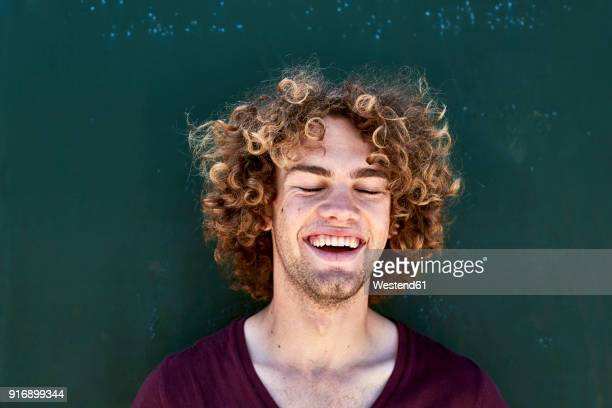 Portrait of laughing young man with curly hair in front of a green wall