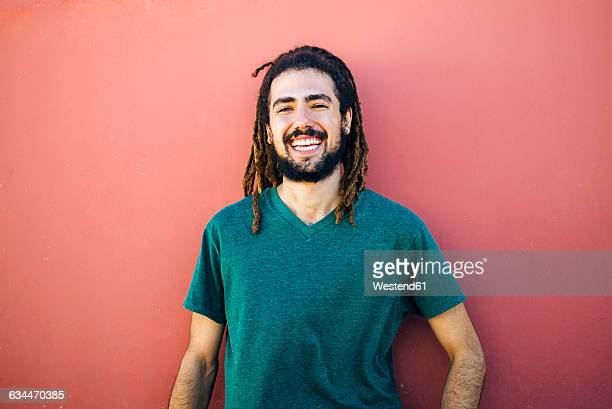 Portrait of laughing young man with dreadlocks and beard in front of a red wall