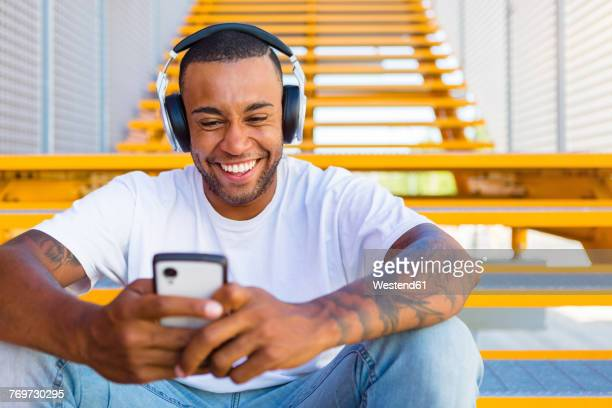 portrait of laughing young man with headphones sitting on stairs looking at smartphone - human body part stock pictures, royalty-free photos & images