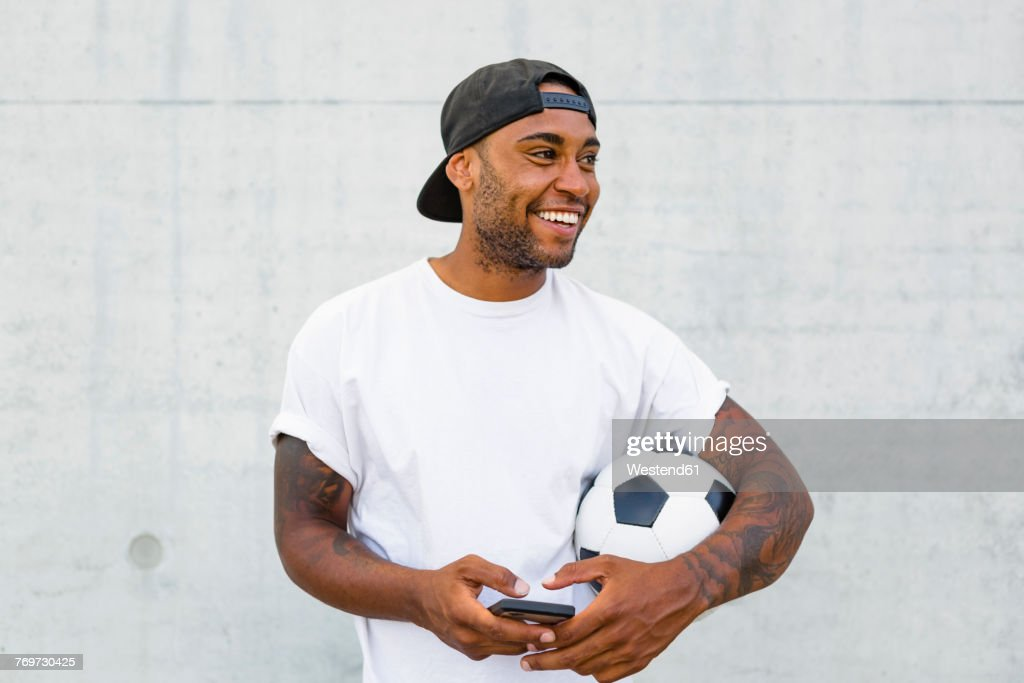 Portrait of laughing young man with soccer ball and cell phone : Stock Photo