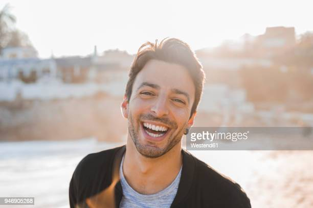 Portrait of laughing young man with stubble on the beach at sunset