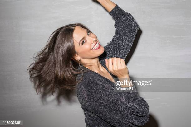 portrait of laughing young woman dancing at party - formal portrait stock-fotos und bilder
