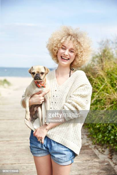 Portrait of laughing young woman holding dog on her arms