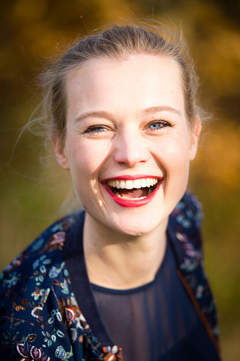 Portrait of laughing young woman in autumn - gettyimageskorea