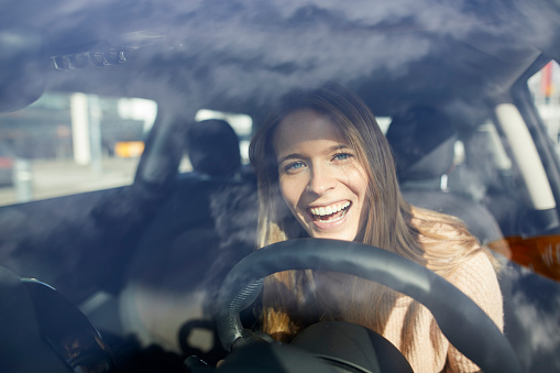 Portrait of laughing young woman in car - gettyimageskorea