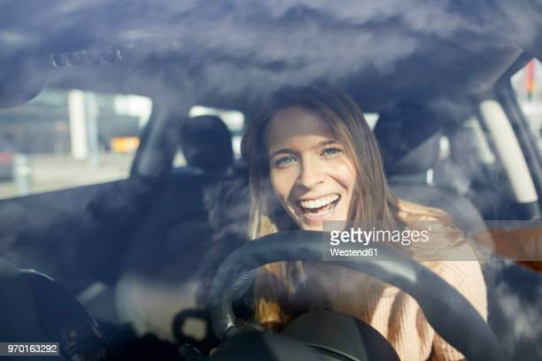 Portrait of laughing young woman in car