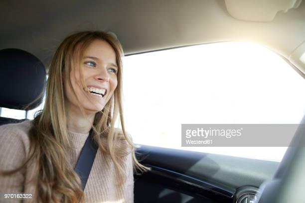 portrait of laughing young woman in car - fahrzeug innenansicht stock-fotos und bilder