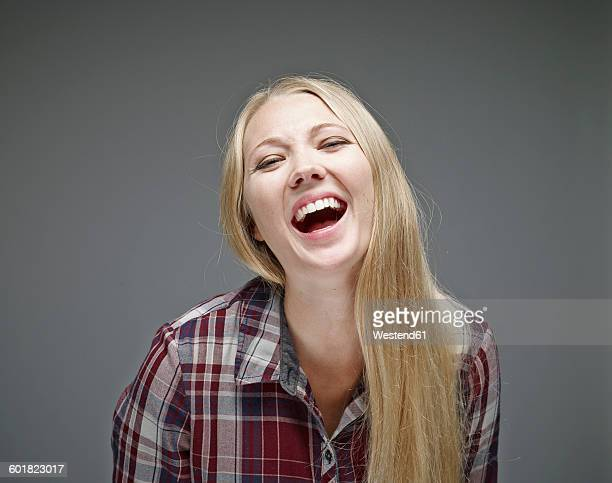 Portrait of laughing young woman in front of grey background