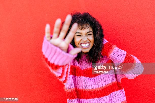 portrait of laughing young woman in front of red wall - focus on background stock pictures, royalty-free photos & images