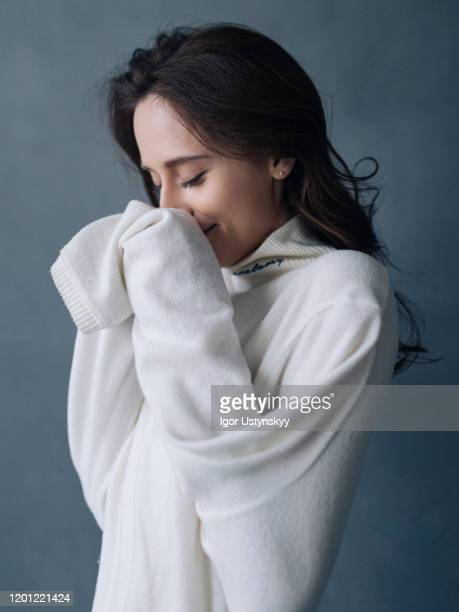 portrait of laughing young woman in sweater - セーター ストックフォトと画像