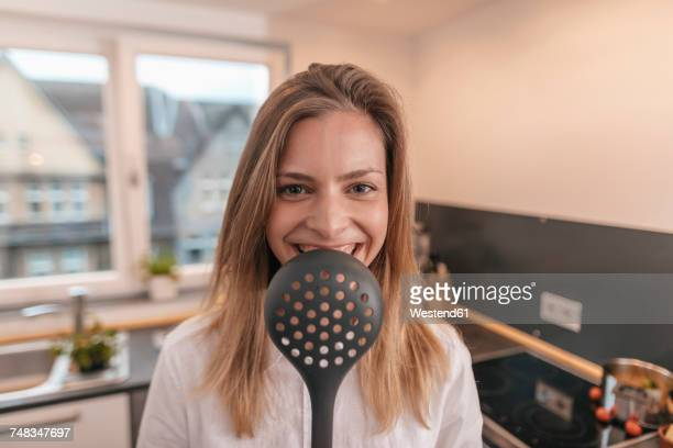 Portrait of laughing young woman in the kitchen