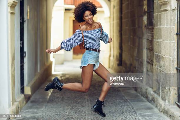 portrait of laughing young woman jumping in the air - shorts stock pictures, royalty-free photos & images