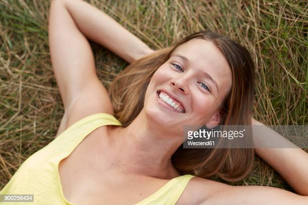 portrait of laughing young woman lying on a meadow - liegen stock-fotos und bilder