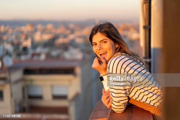 portrait of laughing young woman on balcony at sunset - inclinar se pose imagens e fotografias de stock
