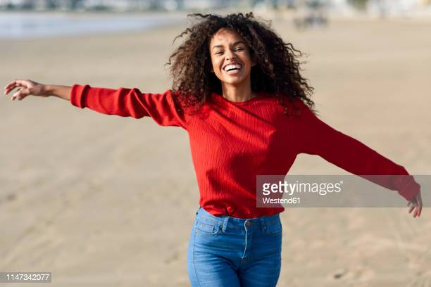 portrait of laughing young woman on the beach - ausgestreckte arme stock-fotos und bilder