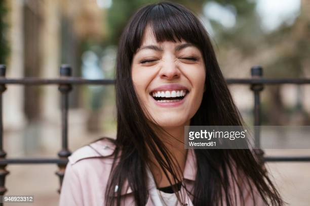 portrait of laughing young woman outdoors - lachen stockfoto's en -beelden