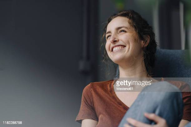 portrait of laughing young woman sitting on lounge chair at home - cheerful stock-fotos und bilder