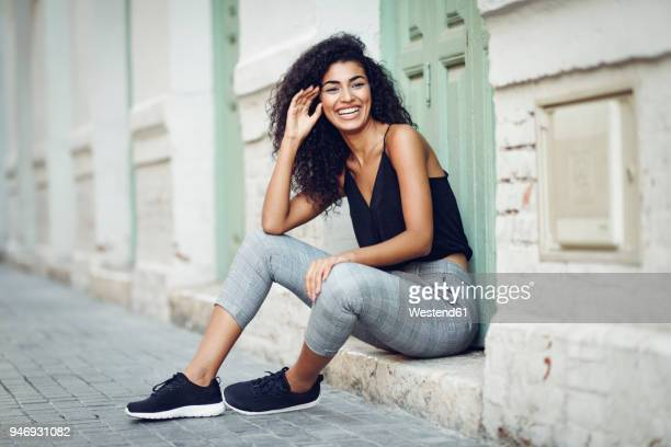 portrait of laughing young woman sitting on step in front of an entrance door - north african ethnicity stock pictures, royalty-free photos & images