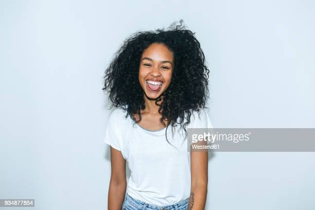 portrait of laughing young woman sticking out tongue - jonge vrouw stockfoto's en -beelden