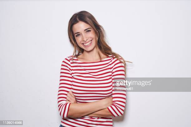 portrait of laughing young woman wearing red-white striped shirt against white background - fröhlich stock-fotos und bilder