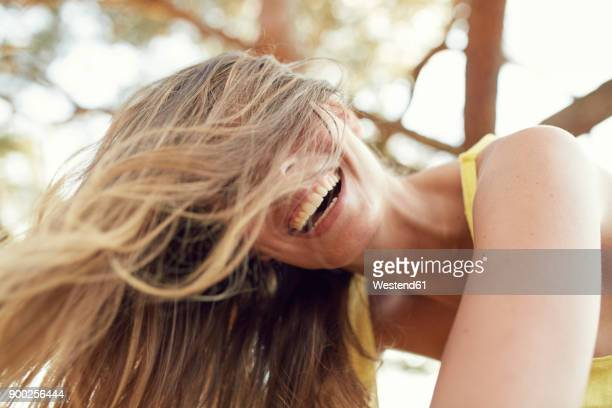 portrait of laughing young woman with blowing hair - haar stock-fotos und bilder